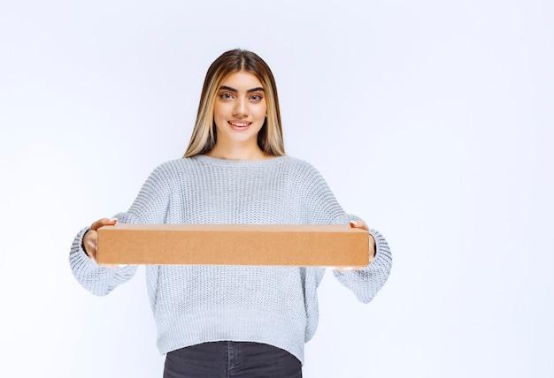 Meisje heeft een kartonnen pakket afgeleverd bij de klant.