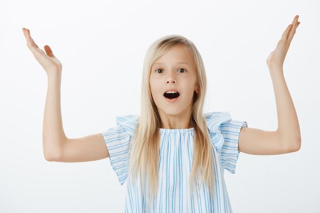 Meisje heeft geen idee hoe ze moet antwoorden, omdat ze niet voorbereid is op vragen van leraren. portret van verward opgewonden schattig kind met blond haar, palmen opheffend en ondervraagd bij het horen van stom idee over grijze muur