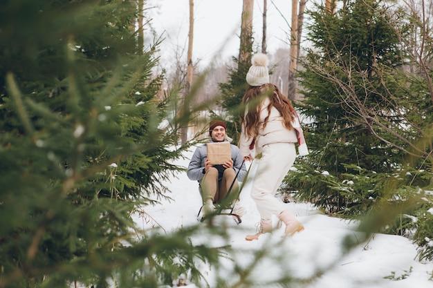 Meisje heeft plezier met het rijden van haar geliefde vriendje op een slee met cadeaus in een winternaaldbos