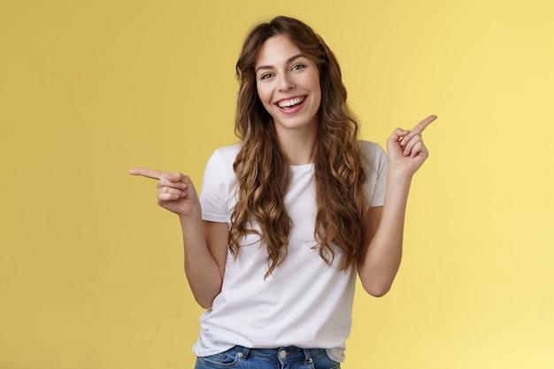 Meisje heeft twee suggesties die zijwaarts wijzen. vrolijke charismatische, gekrulde aantrekkelijke vrouw die naar links wijst, wijsvingers naar rechts, introduceert promoproducten met een glimlachende, algemeen levendige aanbevelingsadvertentie.