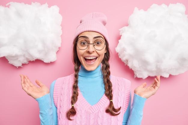 Meisje heft handpalmen op reageert op iets geweldigs glimlacht breed draagt ronde bril hoed en vest hoort uitstekend nieuws uiten goede emoties geïsoleerd op roze
