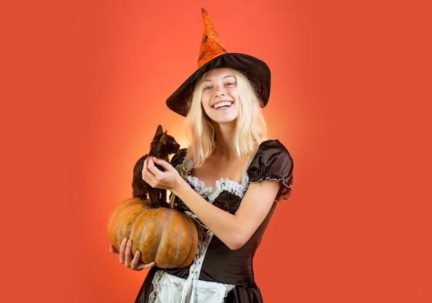 Meisje heks speelt met zwart katje halloween heks in zwarte hoed. zwarte kat zit op een pompoen. meisje heks speelt met zwart katje. huishoudster.