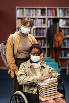 Meisje helpt haar collega in rolstoel een boek te kiezen voor een project
