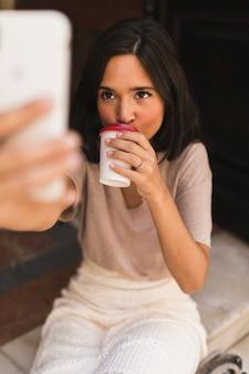 Meisje het drinken koffie die zelfportret van slimme telefoon neemt