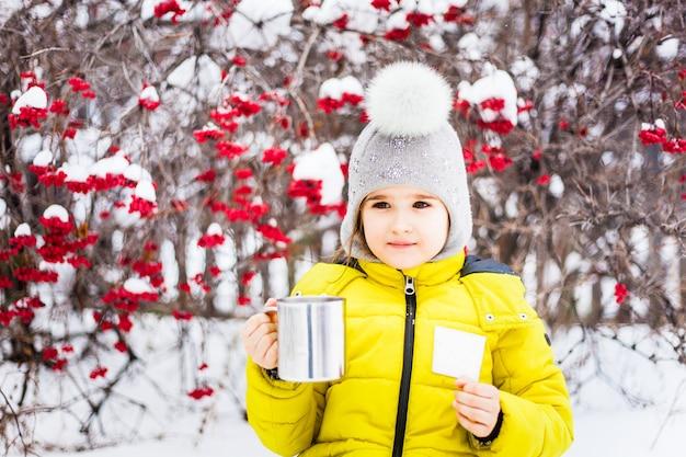Meisje het drinken van thee in de winter, of drink van een mok, een reismok en sommige koekjes of cakes.