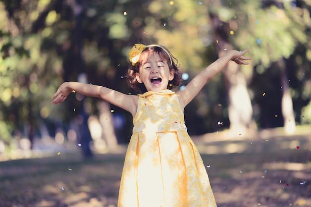 Meisje het gooien van confetti in de lucht