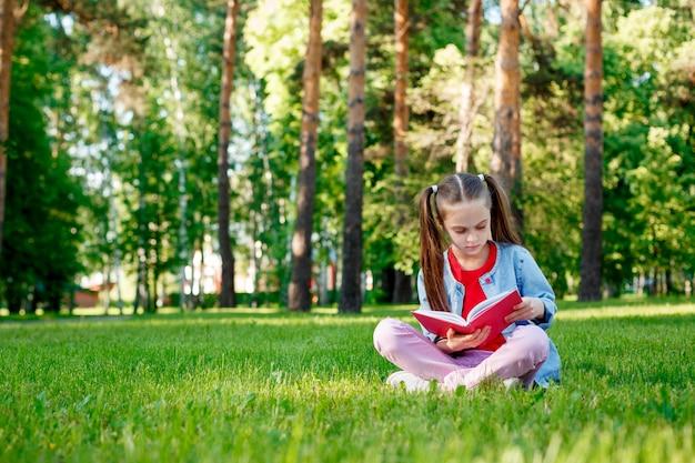 Meisje het lezen van een boek zit op gras in zomerdag in de buitenlucht