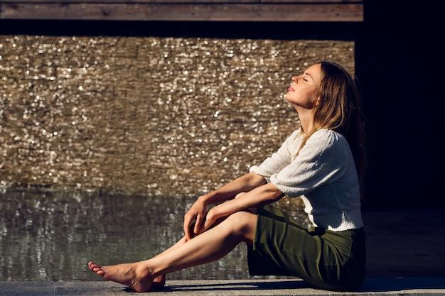 Meisje het ontspannen onder de zon dichtbij het water in wellustige hete dag