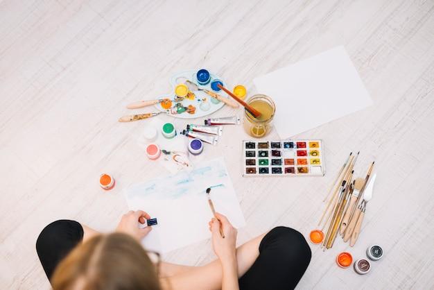 Meisje het schilderen met heldere aquarelle op vloer