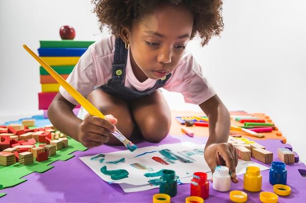 Meisje het schilderen op papier in studio