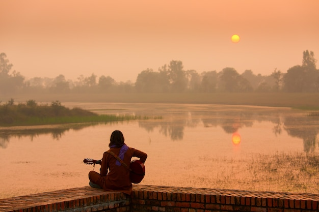 Meisje het spelen gitaar bij zonsondergang