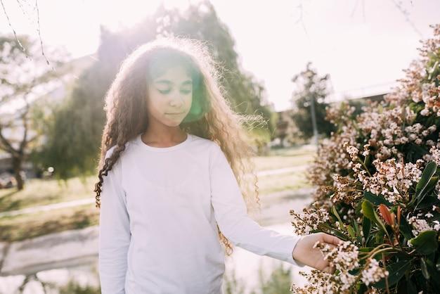 Meisje het spelen met bloemen in tuin