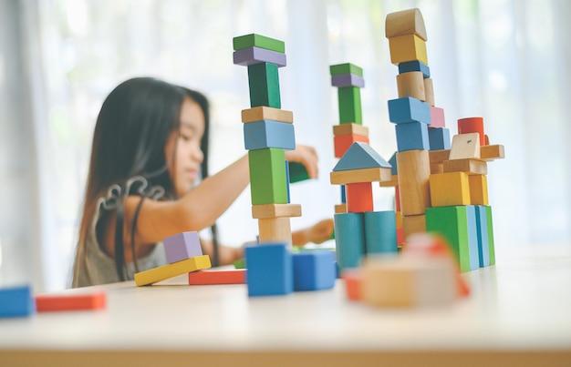 Meisje het spelen met bouwstuk speelgoed blokken die een toren bouwen