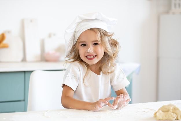 Meisje het spelen met deeg voor koekjes op keuken