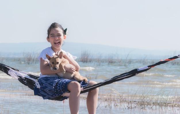 Meisje het spelen met hond op hangmat