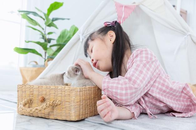Meisje het spelen met kat in de houten mand thuis, vriendschapsconcept.