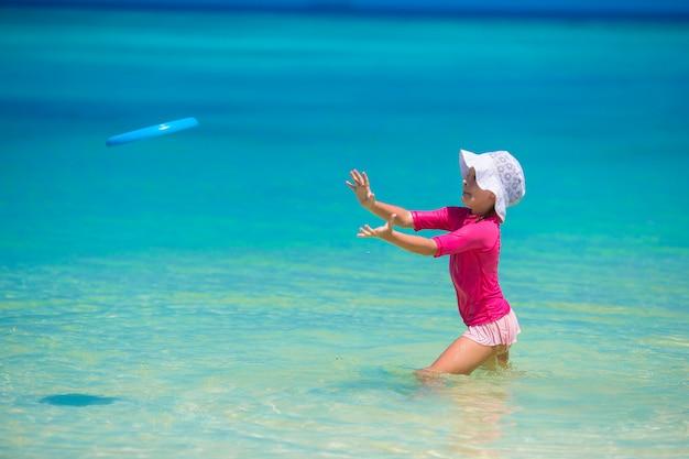 Meisje het spelen met vliegende schijf bij wit strand