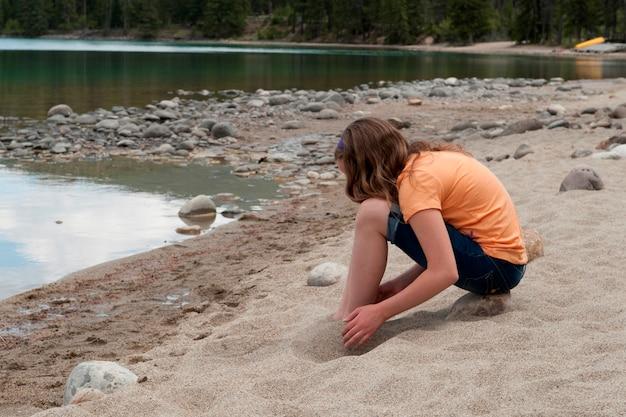 Meisje het spelen met zand bij de oever van het meer, edith lake, jasper national park, alberta, canada