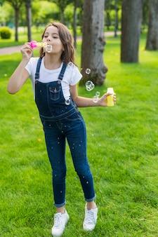 Meisje het spelen met zeepbels in openlucht
