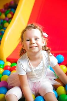 Meisje het spelen op de speelplaats, in het labyrint van kinderen met bal