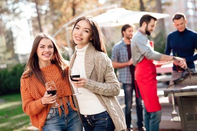 Meisje het stellen bij de camera met wijn tijdens een picknick.