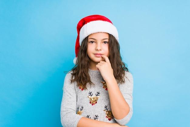 Meisje het vieren kerstmisdag die zijdelings met twijfelachtige en sceptische uitdrukking kijkt.