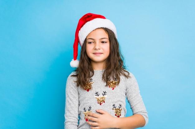 Meisje het vieren kerstmisdag raakt buik, glimlacht zacht, het eten en tevredenheidsconcept.