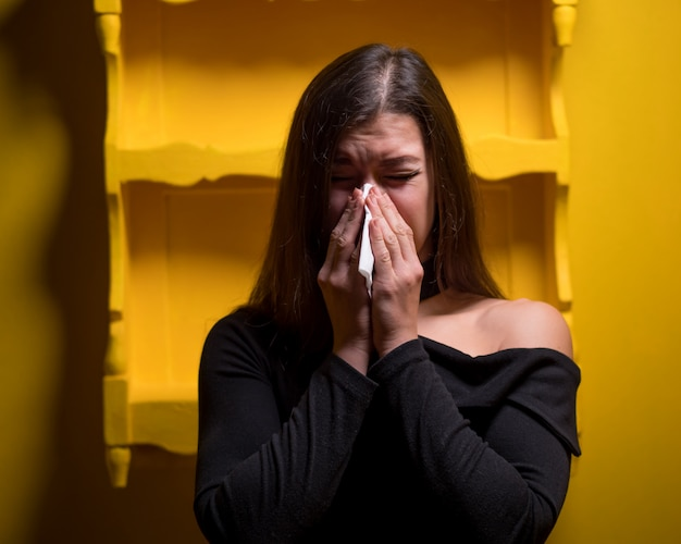 Meisje hoest. vrouw op gele muur