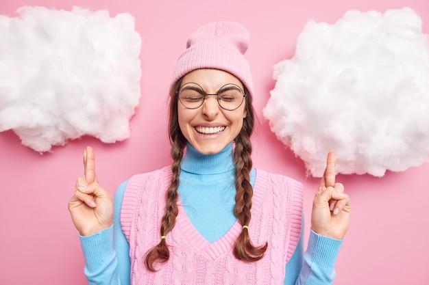 Meisje hoopt op geluk kruist vingers anticipeert op positieve nieuws staat op witte wolken sluit ogen draagt ronde bril hoed en coltrui. mogen mijn dromen uitkomen