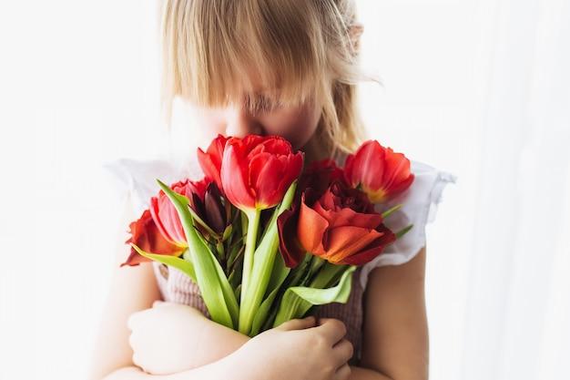 Meisje houden en snuiven boeket van rode tulp bloemen