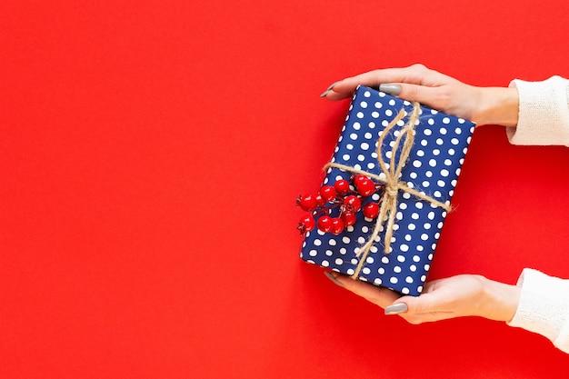 Meisje houdt blauwe geschenkdoos in polka dots met takje meidoorn op een rode achtergrond, prettige kerstdagen en gelukkig nieuwjaar concept, plat lag, bovenaanzicht