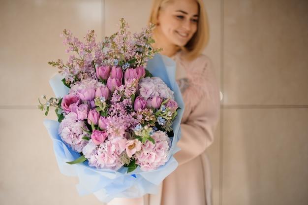 Meisje houdt boeket van pioenrozen, rozen en lila