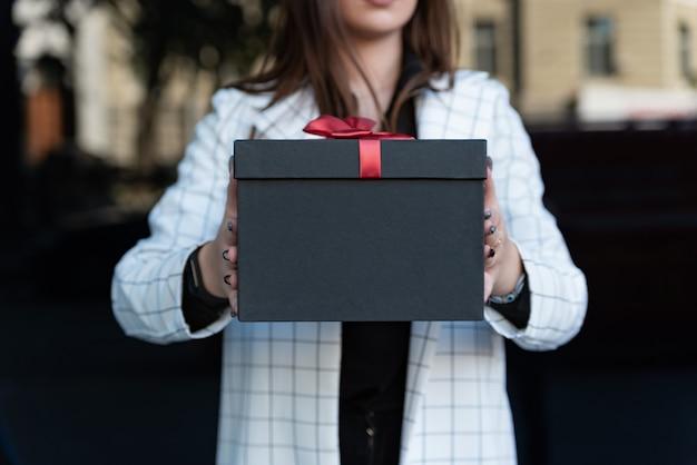 Meisje houdt cadeau. zwarte geschenkdoos met rood lint. detailopname. mooie geschenkdoos in vrouwelijke handen. ruimte kopiëren.