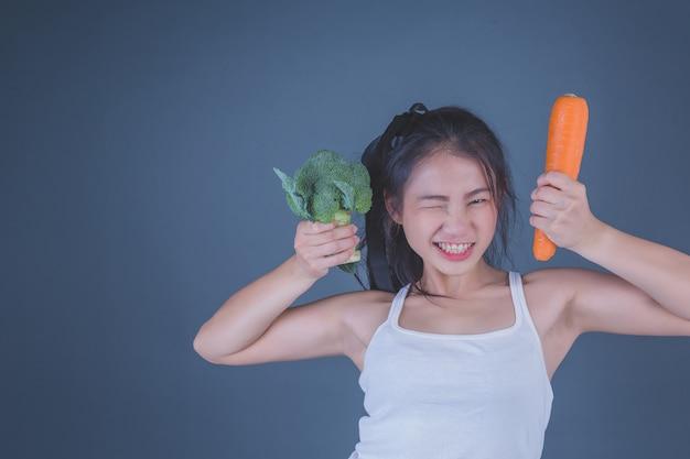 Meisje houdt de groenten op een grijze achtergrond.
