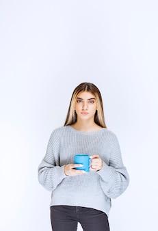 Meisje houdt een blauwe koffiemok vast en promoot het.