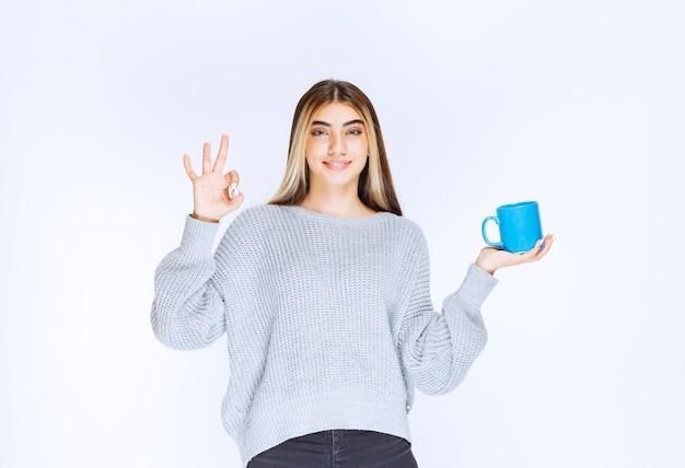 Meisje houdt een blauwe kop thee vast en geniet van de smaak.