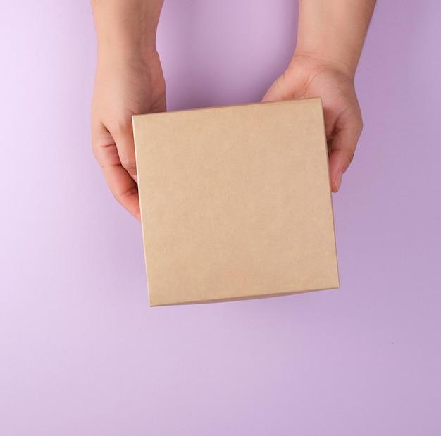 Meisje houdt een bruine vierkante doos op een paarse achtergrond