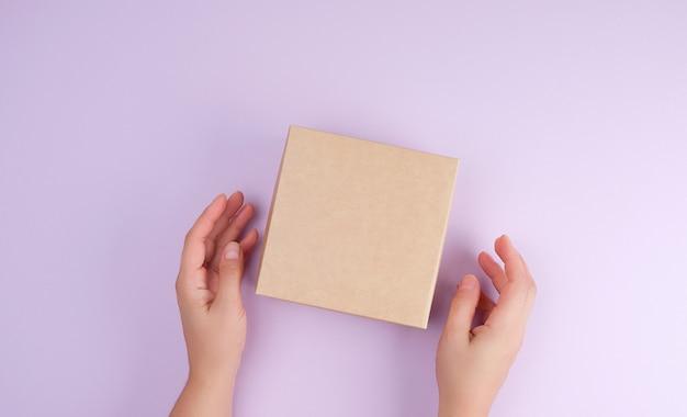 Meisje houdt een bruine vierkante doos