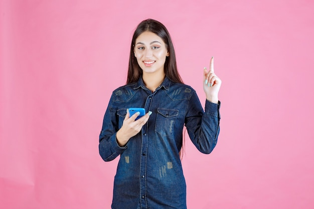 Meisje houdt een gloednieuwe smartphone vast en wijst erop