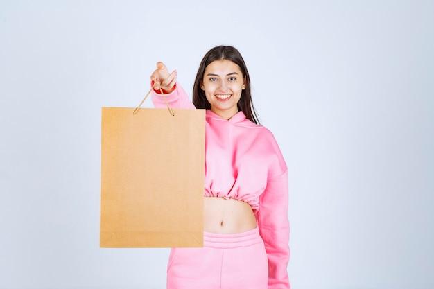 Meisje houdt een kartonnen boodschappentas vast en biedt deze aan de klant aan.