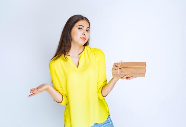 Meisje houdt een kartonnen geschenkdoos vast en voelt zich positief.
