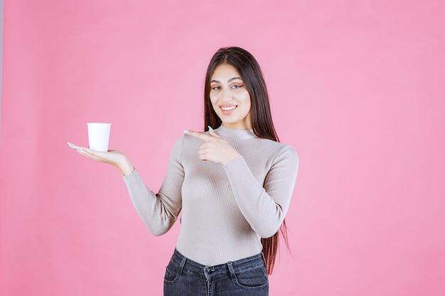 Meisje houdt een koffiekopje vast en wijst erop