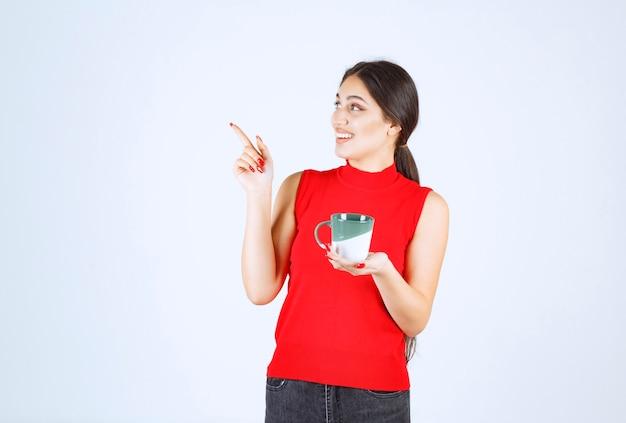 Meisje houdt een koffiemok vast en wijst naar links.