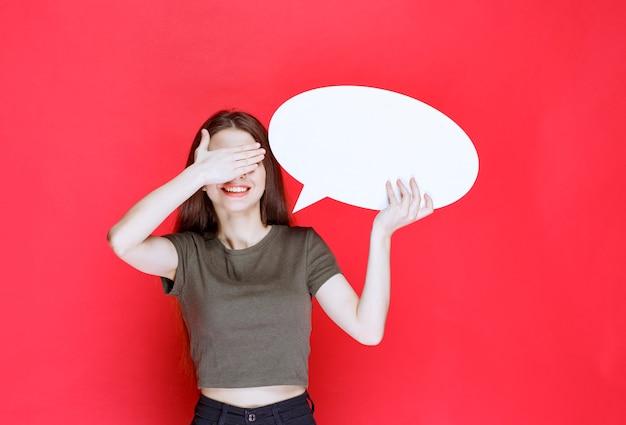 Meisje houdt een leeg ovale infobord vast en sluit haar ogen.