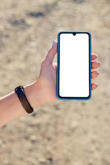 Meisje houdt een mobiele telefoon op vakantie in de natuur. mockup