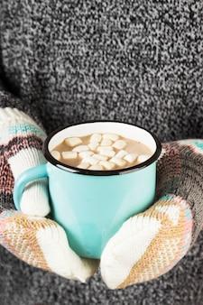 Meisje houdt een mok warme chocolademelk met marshmallows in wanten