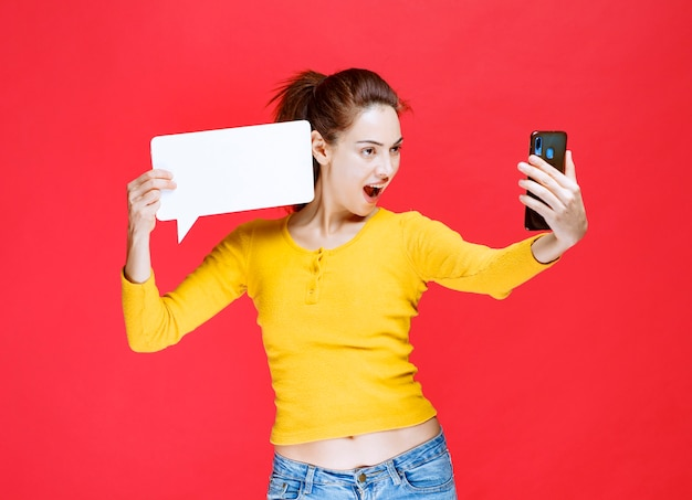 Meisje houdt een rechthoekig infobord vast en voert een videogesprek.