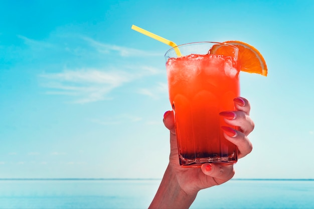 Meisje houdt een rode cocktail vast met een schijfje sinaasappel. jus d'orange in handen van de vrouw op het strand met zee achtergrond