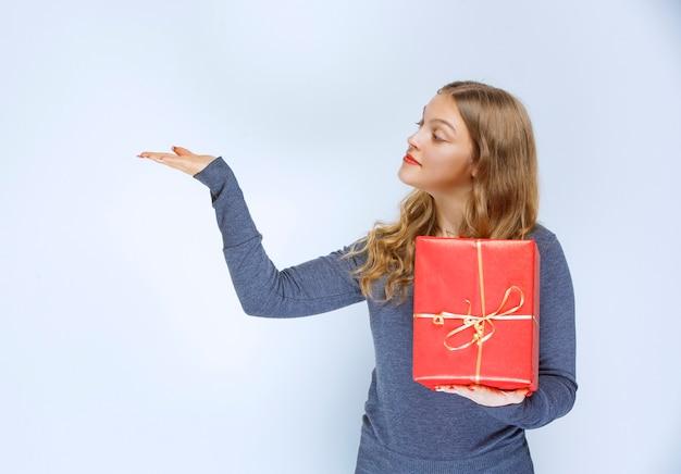 Meisje houdt een rode geschenkdoos vast en wijst naar iemand aan de linkerkant.