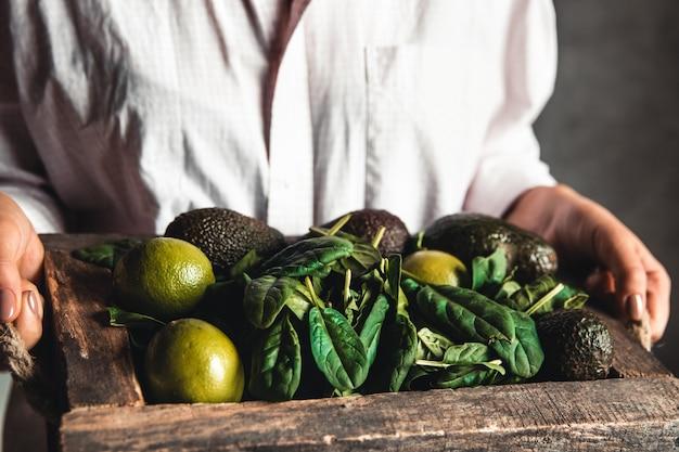 Meisje houdt een smoothie met spinazie, avocado en limoen in een vintage doos. gezond eten, veganistisch, eco.
